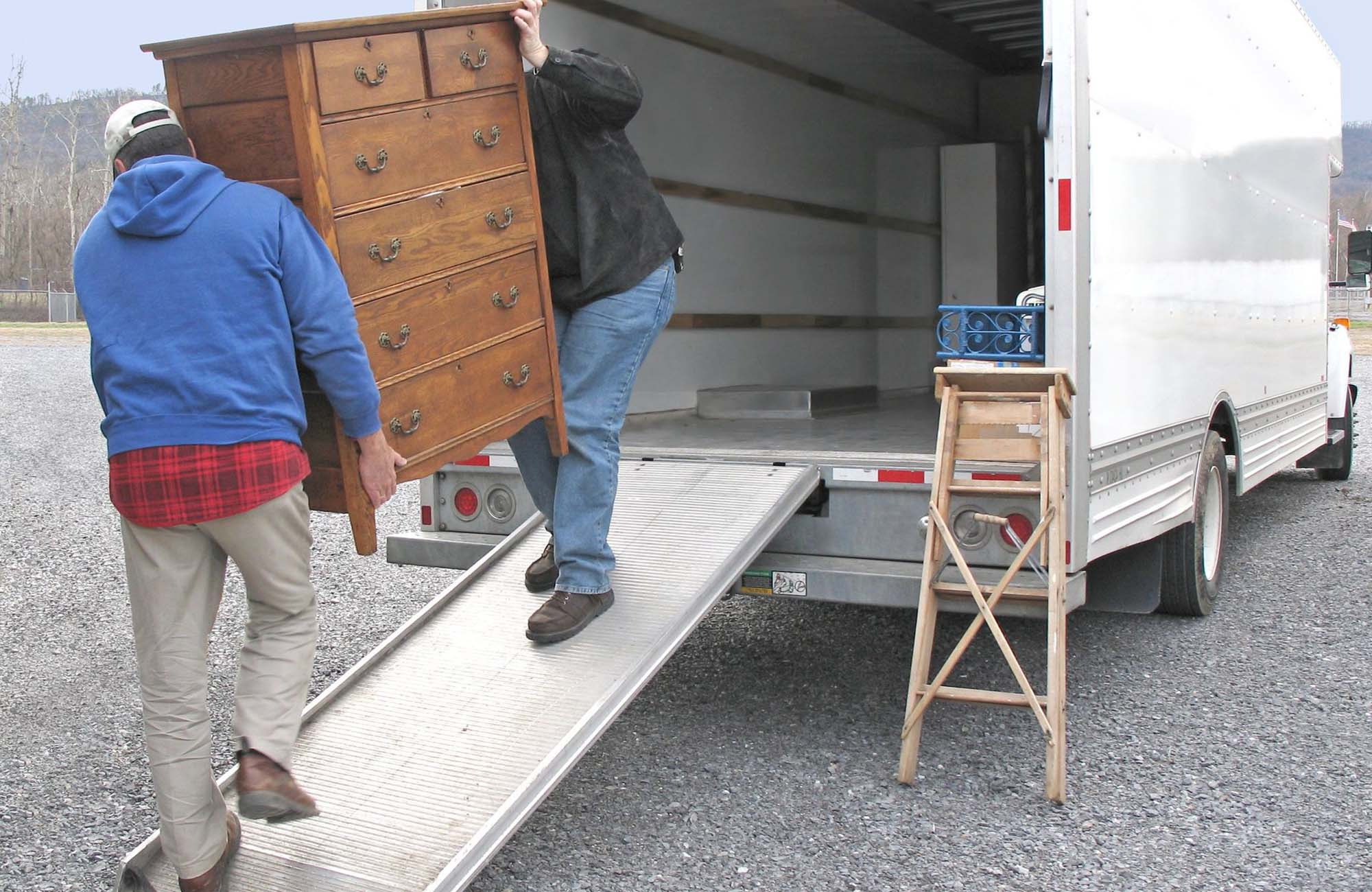 2 men lifting chest of drawers from van